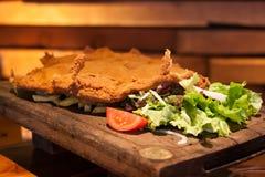 Cachopo,西班牙的阿斯图里亚斯地区的一个典型的盘包括两个大面包小牛肉内圆角用火腿和乳酪填装了 免版税库存图片
