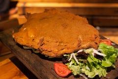 Cachopo en typisk maträtt av den Asturias regionen av Spanien, som består av två stora bröade kalvköttfiléer, fyllde med skinka o Royaltyfri Fotografi