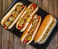 Cachorro quente americano com salmouras, cebolas, ketchup e mostarda Fotos de Stock