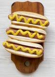 Cachorro quente com mostarda amarela na placa de madeira rústica no fundo de madeira branco, vista superior Configuração lisa, de foto de stock royalty free