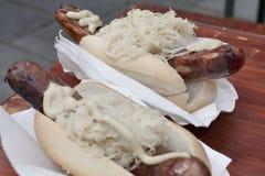 Cachorro quente com mostarda e crauti Imagem de Stock
