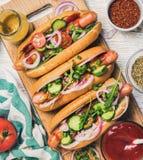 Cachorros quentes caseiros com vegetais, ketchup, mostarda e especiarias Foto de Stock