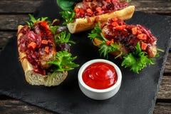 Cachorros quentes com cebola caramelizada, pimentas vermelhas roasted da salsicha de Cumberland Foto de Stock