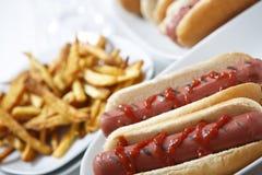 Cachorros quentes com fritadas Fotos de Stock Royalty Free