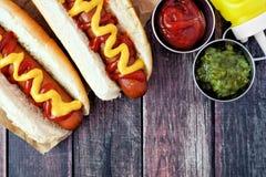 Cachorros quentes com mostarda e ketchup, cena aérea na madeira rústica Fotografia de Stock