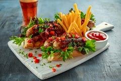 Cachorros quentes da salsicha de Cumberland com cebola caramelizada, pimentas vermelhas roasted, batatas fritas e cerveja Fotos de Stock Royalty Free