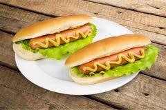 Cachorros quentes saborosos na placa na tabela de madeira Fotografia de Stock