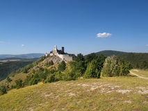 Cachtice castle on hill in distance. Summer view of hill with ruined Cachtice castle in the distance. Cachtice castle is located above Cachtice village, Trencin Stock Image