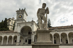Caco statue and clock tower. Caco statue in the background with the clock tower and the castle of Udine, Italy Stock Images