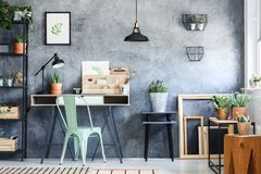 Cactus in ceramic pot. On designed wooden stool in home office with light green chair royalty free stock image