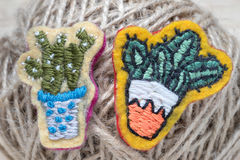 Cactuses. Two cactuses in pots, hand-made embroidery in the form of brooches, on the background of the thread ball Stock Photo