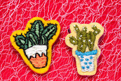 Cactuses. Two cactuses in pots, hand-made embroidery in the form of brooches, on a red background Stock Photography