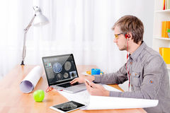 Cad engineer at work. Cad engineer`s workplace with draws, tablet and lamp. Engineer with red headphones working on the laptop with 3d model of turbine for heavy Royalty Free Stock Images