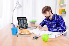 Cad engineer at work. Cad engineer`s workplace with laptop,drawings, notepad and pen, smartphone, apple, croissant, blue cup and lamp. Young engineer developing Stock Images