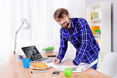 Cad engineer at work. Cad engineer`s workplace with laptop, drawings, notepad and pen, smartphone, apple, croissant, blue cup and lamp. Young engineer developing stock photos