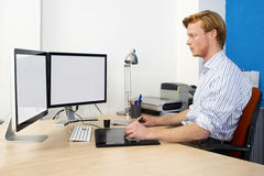 CAD Enginer. Computer Aided Design (CAD) Engineer at work behind two large monotors, using a tablet and graphic pen in product development stock images