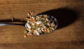 Cada clase de legumbres dentro de una cuchara en una tajadera de madera Imagen de archivo