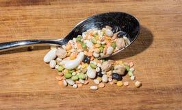 Cada clase de legumbres dentro de una cuchara en una tajadera de madera Fotografía de archivo