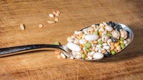 Cada clase de legumbres dentro de una cuchara en una tajadera de madera Foto de archivo libre de regalías