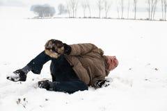 Caída del accidente del invierno del hombre mayor en nieve Imagen de archivo libre de regalías