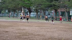 Cada tarde en parque público tiene la gente de la diversidad que juega al fútbol junto en el campo de fútbol para fuerte Cerca de almacen de metraje de vídeo