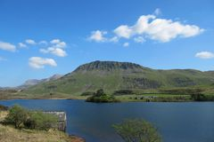 Cadair idris behind a mountain lake bathed in sunshine in snowdonia national park Royalty Free Stock Photography
