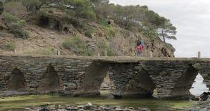 Cadaques, επαρχία Girona, Καταλωνία, Ισπανία Νέος τουρίστας γυναικών που περπατά στην πέτρινη γέφυρα σε Mirador απόθεμα βίντεο