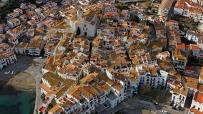 Cadaques Spain. Aerial video. drone is flighting over tiled roofs, narrow streets, white houses and a church. Beautiful. Blue sea. Sunny daylight stock video