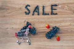 Caddie avec des raisins à l'intérieur, la vente de mot et le signe de pour cent Photographie stock libre de droits
