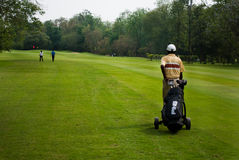 Caddie carrying golfer's club Stock Photography