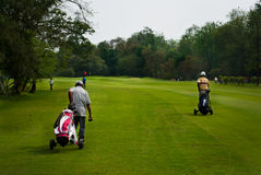 Caddie carrying golfer's club Stock Photo