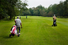 Caddie carrying golfer's club Royalty Free Stock Images