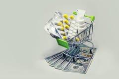 Caddie complètement des pilules de drogue et de médecine sur l'argent du dollar images libres de droits