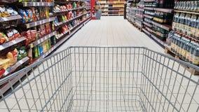 Caddie dans le bas-côté de supermarché Images libres de droits