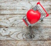 Caddie et coeur sur le bois Images libres de droits
