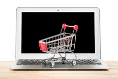 Caddie rouge sur un ordinateur portable d'isolement sur le fond blanc Concept en ligne d'achats d'Internet images libres de droits