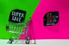 Caddie vert la vente superbe jointe et jusqu'à -70%, font des emplettes maintenant texte sur le fond vert et rose photographie stock