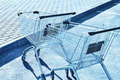 Caddies dans un parking de magasin Tonalité bleue photos libres de droits