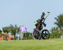 Caddy on a golf course with golfer. Golf caddy trolley and bag on a golf course with golfer in the distance Stock Image