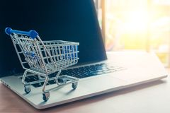 Trolley with a laptop on a wooden desk with light in background. Buy online or shopping on the web concept royalty free stock photo
