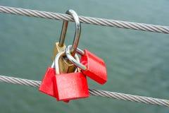 Cadeado do vermelho que penduram em um cabo de aço Imagens de Stock