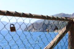 Cadeado e costa rochosa com vila Corniglia de Cinque Terre e mar Mediterrâneo Imagens de Stock Royalty Free