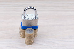 Cadeado em uma pilha de moedas Fotos de Stock