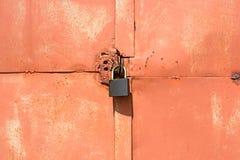 Cadeado em uma porta alaranjada velha da garagem fotografia de stock