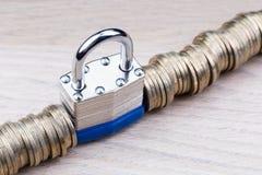 Cadeado entre uma fileira das moedas Fotos de Stock Royalty Free