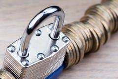 Cadeado entre uma fileira das moedas Imagens de Stock