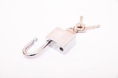 Cadeado metálico com três chaves no buraco da fechadura Fotografia de Stock Royalty Free