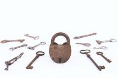Cadeado oxidado antigo com a coleção das chaves isolada no fundo branco Imagens de Stock Royalty Free