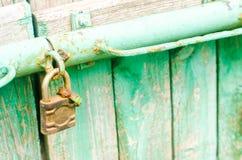 Cadeado oxidado do ferro velho na porta de madeira verde fotos de stock royalty free