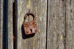 Cadeado oxidado em um prego oxidado Fotografia de Stock Royalty Free